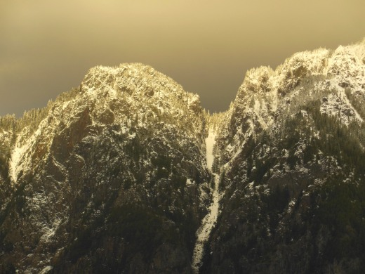 A spotlight lit the new snow covering the haystack peak and dusting the evergreen trees on the moody Spring-like day.